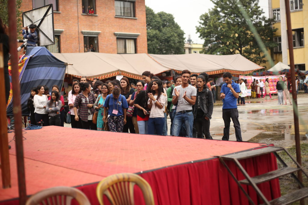 Some Audiences enjoying the performance while other visitors visiting the stalls for information.